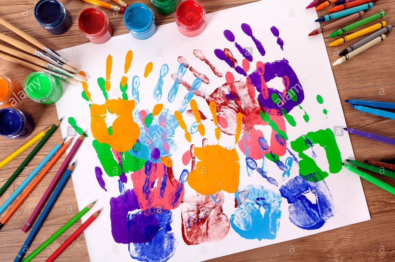 painted-handprints-with-art-and-craft-equipment-on-a-school-table-MB67JT